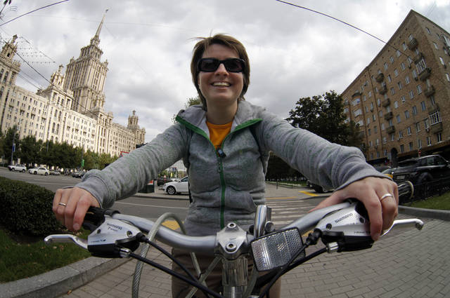 "In this Aug. 31, 2012, photo, AP newswoman Nataliya Vasilyeva rides her bicycle on her way to the bureau in Moscow. The famous soviet style hotel ""Ukraine"" is visible at rear left. ""Riding a bike in Moscow is a completely different experience from cycling in any other European city,"" explains Vasilyeva. ""With no bike lanes but plenty of road rage, most cyclists in Moscow, myself included, keep off the streets and stay on the sidewalk."" But while cycling on the pavement, you need to watch out not only for pedestrians and baby carriages but for the sudden opening of car doors. (AP Photo/Alexander Zemlianichenko)"