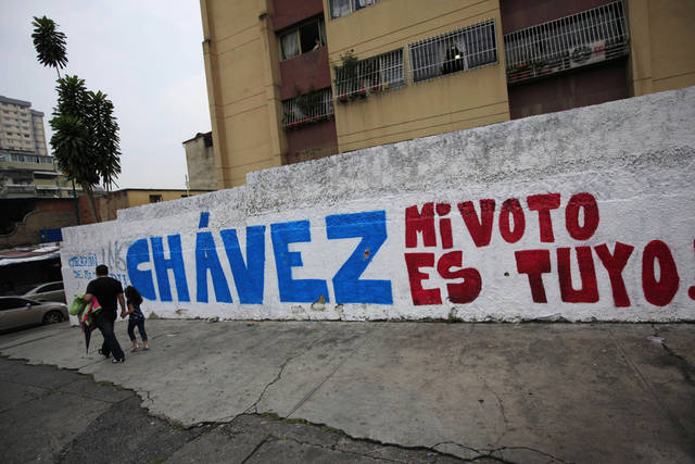 "People pass a mural that reads in Spanish ""Chavez my vote is yours,"" referring to Venezuela's President Hugo Chavez, in Caracas, Venezuela, Friday, Oct. 5, 2012. Venezuelans will head to the polls Sunday to vote in their country's presidential election, deciding on whether to keep Chavez or seek change with opposition candidate Henrique Capriles. (AP Photo/Ariana Cubillos)"