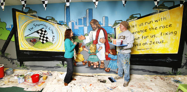 Jennifer Grimes, children�s minister at Oakcrest Church of Christ, 1111 SW 89, visits with Bob Palmer of Palmer Studios as Palmer paints a mural reflecting the church�s children�s ministry called �Starting Line Kids.�  Photos by Paul B. Southerland, THE OKLAHOMAN