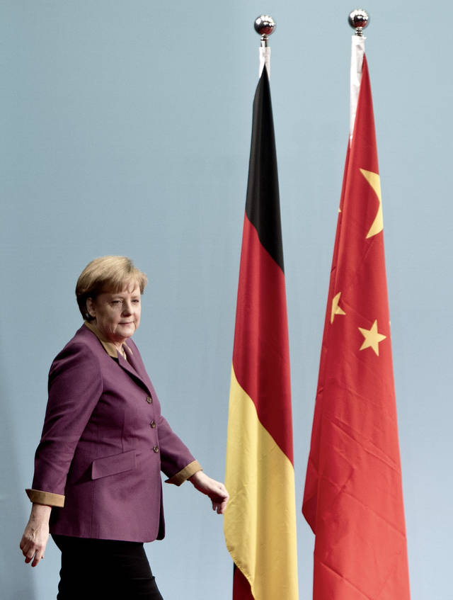 German Chancellor Angela Merkel walks near German and China national flags as she arrives to deliver a speech at the Chinese Academy of Social Science in Beijing, China, Thursday, Feb. 2, 2012. Merkel called Thursday on China, the biggest buyer of Iranian oil, to use its influence to persuade Tehran to renounce possible nuclear weapons ambitions. (AP Photo/Andy Wong)