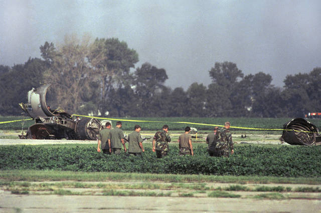 FILE - In this July 20, 1989, file photo, Iowa Air National Guard soldiers search a bean field near the burnt engine of a United Airlines DC-10 that crash-landed, killing 111 people, at the airport in Sioux City, Iowa. Dennis Fitch, of St. Charles, Ill., the pilot who happened to be a passenger and helped save 184 people after the crash, died May 7, 2012, after suffering from brain cancer. He was 69. (AP Photo/James Finley, File)