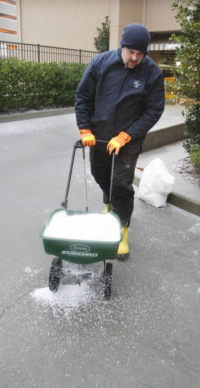 Jeff Blackburn, maintenance engineer at the Skirvin Hotel, spreads de-icer at the Skirvin Hilton Hotel in downtown Oklahoma City early Thursday, Dec. 24, 2009. Photo by Paul B. Southerland, The Oklahoman