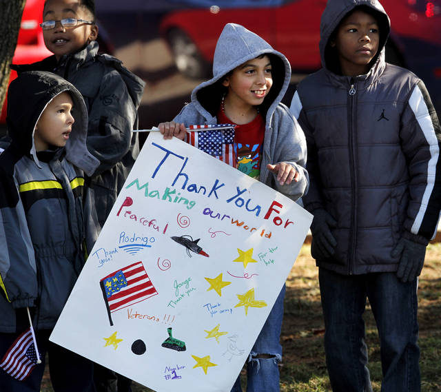 Students from Soldier Creek Elementary School carry flags and hold signs as parade moves past their school at SE 15 and Douglas. The city of Midwest City teamed with civic leaders and local merchants to display their appreciation for veterans and active military forces by staging a hour-long Veteran's Day parade that stretched more than a mile and a half along three of the city's busiest streets Monday morning, Nov. 12, 2012. Hundreds of people lined the parade route, many of them waving small American flags that had ben distributed by volunteers who marched near the front of the parade. A fly-over performed by F-16s from the138th Fighter Wing, Oklahoma Air National Guard unit in Tulsa thrilled spectators. Five veterans representing military personnel who served in five wars and military actions served as  Grand Marshals for the parade. Leading the parade was the Naval Reserve seven-story American flag, carried by 100 volunteers from First National Bank of Midwest City, Advantage Bank and the Tinker Federal Credit Union. The flag is 50 feet by 76 feet, weighs 110 pounds and was sponsored by the MWC Chapter of Disabled American Veterans. Photo by Jim Beckel, The Oklahoman