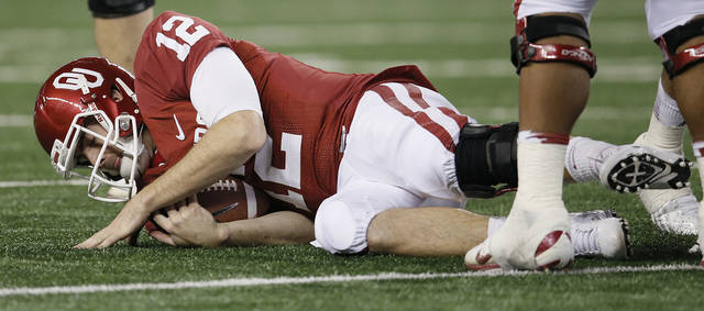 Oklahoma's Landry Jones (12) hits the turf after a sack during the college football Cotton Bowl game between the University of Oklahoma Sooners (OU) and Texas A&M University Aggies (TXAM) at Cowboy's Stadium on Friday Jan. 4, 2013, in Arlington, Tx. Photo by Chris Landsberger, The Oklahoman