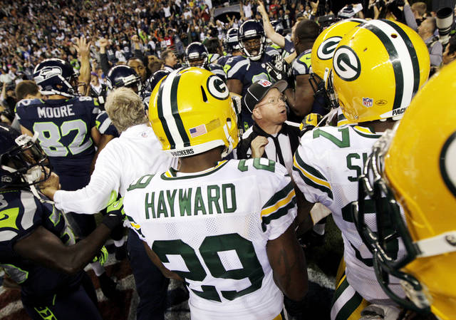 Officials try to sort out the final play of an NFL football game between the Green Bay Packers and the Seattle Seahawks as players and coaches swarm the field, Monday, Sept. 24, 2012, in Seattle. After a period of confusion, a Seahawks touchdown by wide receiver Golden Tate was allowed to stand for a 14-12 win. (AP Photo/Ted S. Warren) ORG XMIT: SEA129