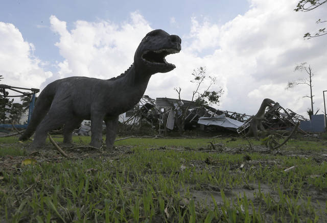 Sculptures of dinosaurs are left standing at a park which was damaged by the recent typhoon that hit New Bataan township, Compostela Valley in southern Philippines Sunday Dec. 9, 2012. The number of missing in the wake of the typhoon that devastated parts of the southern Philippines has jumped to nearly 900 after families and fishing companies reported losing contact with more than 300 fishermen in the South China Sea and Pacific Ocean, officials said Sunday. (AP Photo/Bullit Marquez)