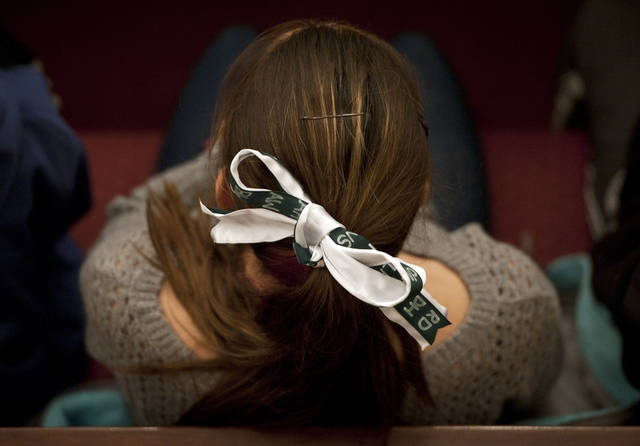 A young woman wears a green and white bow, the colors of Sandy Hook Elementary School, in her hair with the initials of the victims names from the Dec. 14, 2012 shooting during an interfaith a sermon at Newtown Congregational Church in Newtown, Conn., Sunday, Jan. 20, 2013.  The Rev. James A. Forbes, Jr., who led one of the country�s most prominent liberal Protestant churches, is speaking at the church to honor the victims of last month�s school shooting and the legacy of the Rev. Martin Luther King Jr. (AP Photo/Jessica Hill)