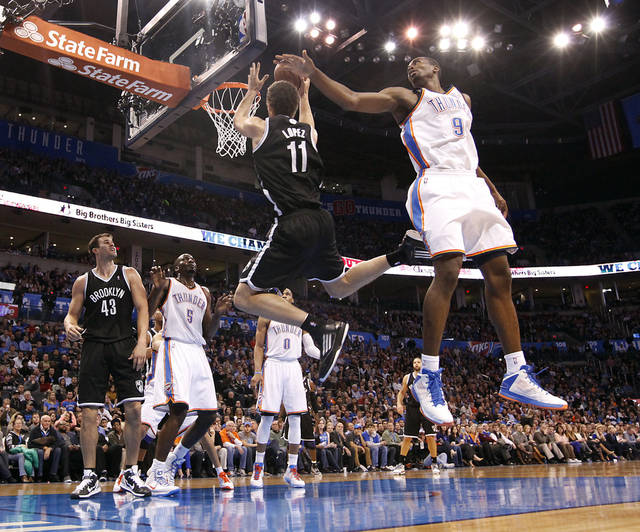 Oklahoma City&#039;s Serge Ibaka (9) tries to defend on Brooklyn Nets&#039; Brook Lopez (11) during the NBA basketball game between the Oklahoma City Thunder and the Brooklyn Nets at the Chesapeake Energy Arena on Wednesday, Jan. 2, 2013, in Oklahoma City, Okla. Photo by Chris Landsberger, The Oklahoman