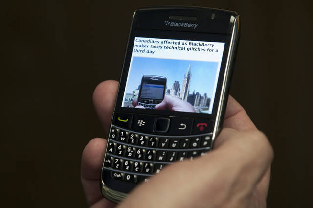 FILE - In this Oct. 12, 2011, file photo, A Blackberry subscriber holds a Research in Motion Blackberry in Ottawa. BlackBerry users will be able to make free voice calls over a Wi-Fi network using the popular BBM messaging service. Research In Motion Ltd. announced Wednesday that it�s adding the feature to BBM. Users will be able to switch back and forth from a text chat to a(AP Photo/The Canadian Press, Adrian Wyld)