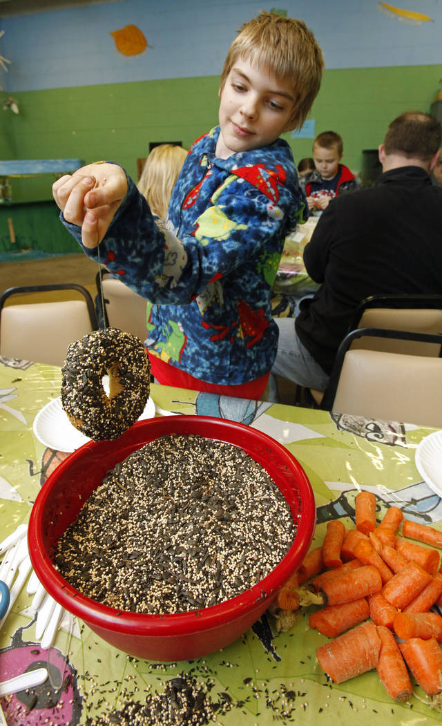 Ryan Harrison, 11, pulls his shortning covered bagel out of bird seed making a bird feeder as visitors help string fruit and hang it on trees for birds and deer that live in Martin Park during a free class on Saturday, Dec. 17, 2011, in Oklahoma City, Okla.   Photo by Steve Sisney, The Oklahoman