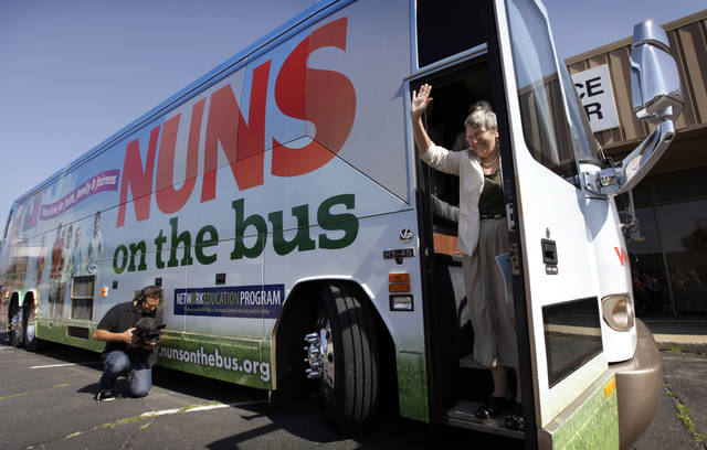 Sister Simone Campbell, executive director of Network, waves as she steps off the bus during a stop on the first day of a 9-state Nuns on the Bus tour, Monday, June 18, 2012, in Ames, Iowa. The group of Roman Catholic nuns say they're not opposing any particular candidate but that their fight is with a Republican proposed federal budget they say hurts the poor and needy. (AP Photo/Charlie Neibergall)