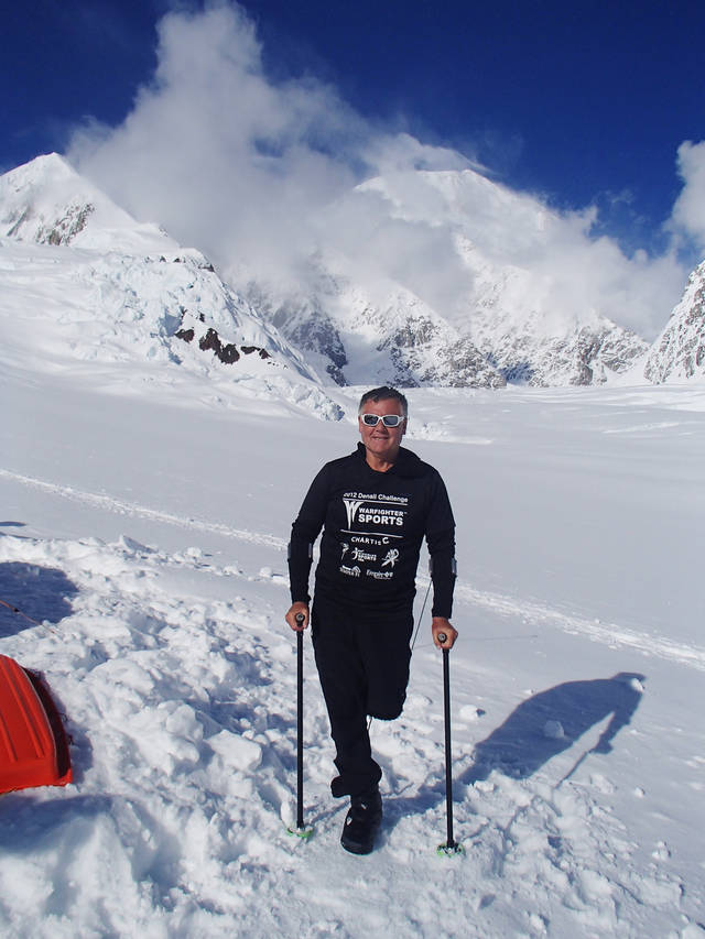 In this June 13, 2012 photo released by Disabled Sports USA, shows Kirk Bauer, 64, a climber and executive director of Disabled Sports USA, poses in front of Mount McKinley, Alaska. He lost his leg during the Vietnam War. He is one of five wounded warriors, who by their own admission have four good legs among them, who are attempting to climb the 20,320-foot mountain in the Alaska Range. All but one lost limbs in American conflicts ranging from Vietnam to Afghanistan (AP Photo/Disabled Sports USA)