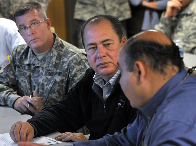 West Virginia Gov. Earl Ray Tombli is briefed by Jimmy Gianato, right, state director of homeland security and emergency management, at the National Guard Armory before a teleconference with officials scattered throughout storm-affected areas of West Virginia, Wednesday, Oct. 31, 2012, in Charleston, W.Va. At left is West Virginia National Guard Adjutant Gen. James Hoyer. (AP Photo/Charleston Daily Mail, Craig Cunningham)