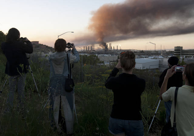 The curious gather on a hillside in Point Richmond, Calif., to photograph the the fire in an oil unit at the Chevron refinery in Richmond, Calif., Monday, Aug. 6, 2012. Officials have told residents of two Northern California cities to shelter-in-place as a fire at a Chevron refinery in Richmond releases plumes of black smoke. (AP Photo/D. Ross Cameron/) (AP Photo/The Contra Costa Times, D. Ross Cameron) NO SALES MAGS OUT LOCALS PLEASE CREDIT