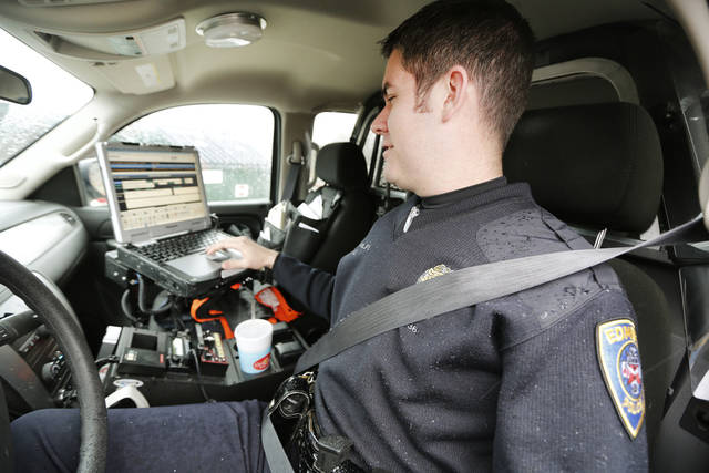 Edmond police officer Paul Phillips works on a report using his laptop computer in his car in front of Orvis Risner Elementary School.  PHOTO BY STEVE GOOCH, THE OKLAHOMAN