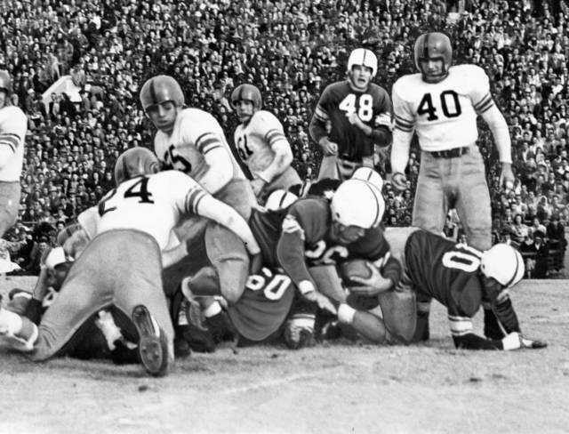 This sideline action shot shows University of Oklahoma quarterback Jack Mitchell (26) squirming through the line to score OU's first touchdown in the 1947 Bedlam game. Oklahoma A&M's Arlen McNeil (24) is poised to make the belated tackle. The Sooners beat the Cowboys 21-13 in Norman. OKLAHOMAN ARCHIVE PHOTO
