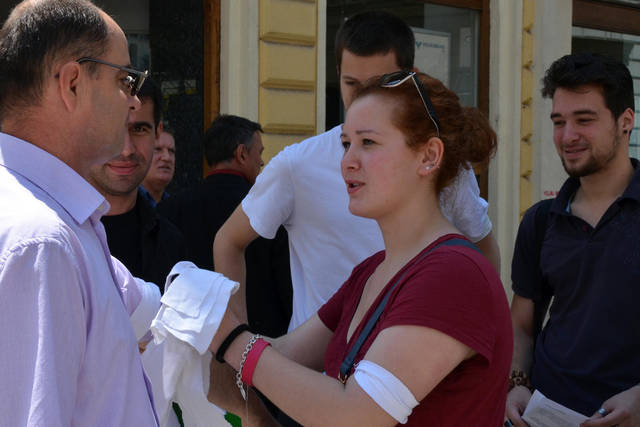 "Bosnian youth, members of NGO ""Izvor"" tie white bandanas on passing citizens of Sarajevo, on Thursday, May 31, 2012. The ""white bandana day"" campaign invites people to put an end to genocide denial by marking 20 years since the day, in the beginning of Bosnia's inter-ethnic war 1992-95, when Bosnian Serb authorities issued an order for non-Muslim population of Western-Bosnian town of Prijedor to clearly mark their houses with white flags and to wear white bandanas in public. This was the second time in modern history that such a method of public segregation was implemented in Europe. The first case was recorded in 1939, in Nazi occupied Poland, when Polish Jews were ordered to be marked in similar fashion. (AP Photo/Amel Emric)"