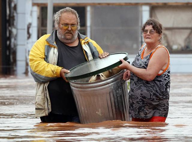 Flooding kills at least two, forces many from homes