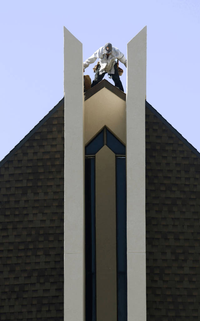 Roofer Juan Carlos Zuniga seals the last shingles onto the peak of the roof of the Chapel Hill United Methodist Church in Oklahoma City, OK, Monday, Aug. 9, 2010. By Paul Hellstern, The Oklahoman
