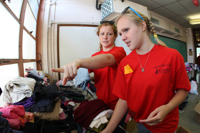 In this photo provided by Samford University, Annie Criswell and Jessica Fleming sort clothes for distribution to tornado victims in Pratt City, Ala., Saturday, April 30, 2011. Criswell and Fleming were among several Samford University students who volunteered at Scott Elementary School. (AP Photo/Samford University, Caroline Summers)