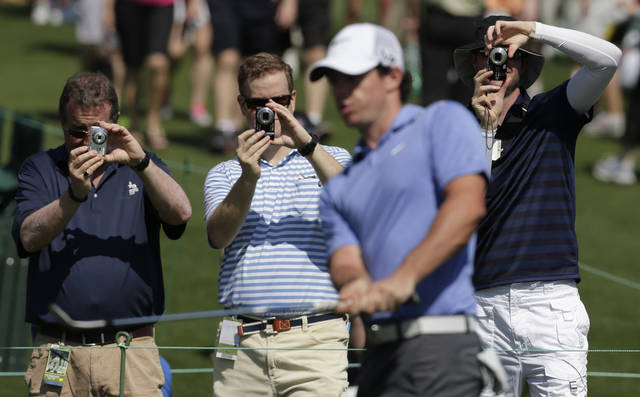 Spectators take photos of Rory McIlroy, of Northern Ireland, as he chips on the seventh green during a practice round for the Masters golf tournament Tuesday, April 9, 2013, in Augusta, Ga. (AP Photo/Charlie Riedel)