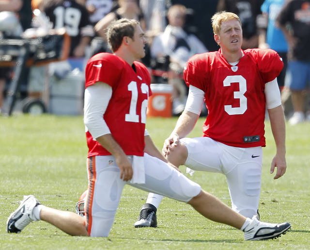 Cleveland Browns quarterbacks Brandon Weeden, right. and Colt McCoy stretch during an NFL football training camp in Berea, Ohio Monday July 30, 2012. (AP Photo/Ron Schwane)