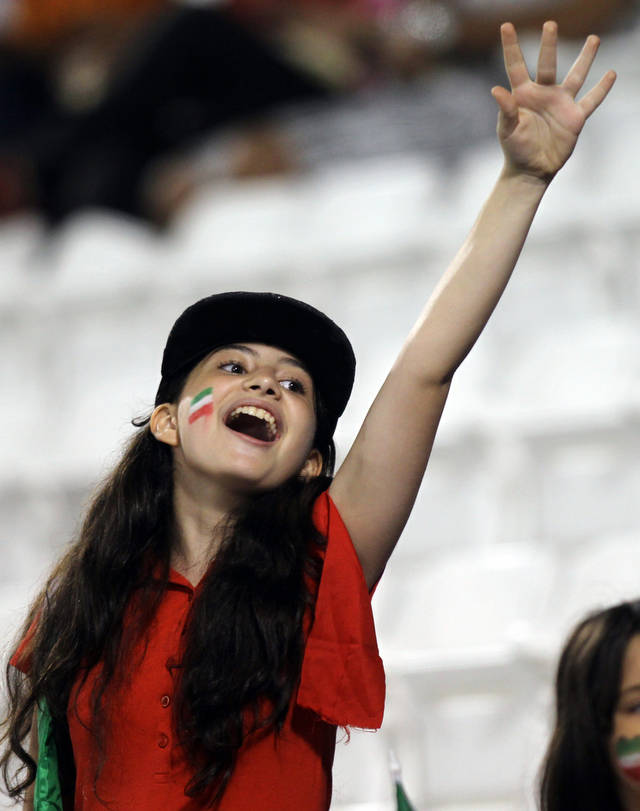 An Iranian young woman fan celebrates her team's winning during their 2014 World Cup Asian zone qualifying football match between Qatar and Iran at the Al-Sadd stadium in Doha on, Tuesday,June, 4, 2013. (AP Photo/Osama Faisal)