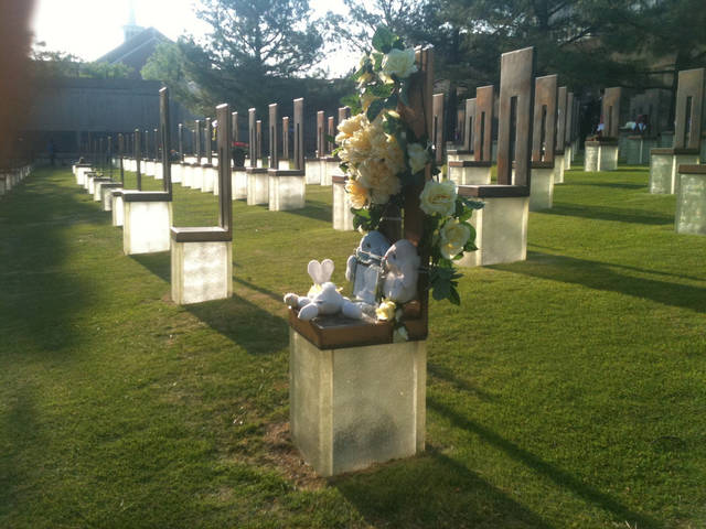 Flowers and stuffed animals on a chair at the Oklahoma City National Memorial Tuesday morning - Photo by John Clanton