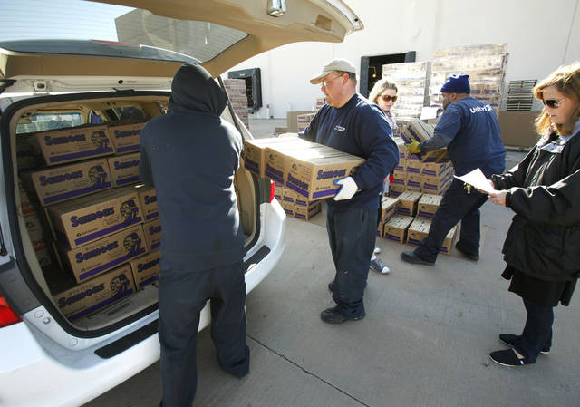 Workers load dozens of boxes into a van as the first day of Girl Scout cookie distribution begins in Oklahoma City, OK, Friday, Jan. 20, 2012. By Paul Hellstern, The Oklahoman