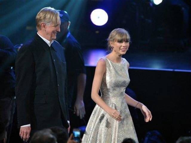 T Bone Burnett, left, and Taylor Swift, right walk to the stage to accept the award for song written for visual media for &quot;Safe and Sound&quot; (From The Hunger Games) at the 55th annual Grammy Awards on Sunday, Feb. 10, 2013, in Los Angeles. (Photo by John Shearer/Invision/AP)