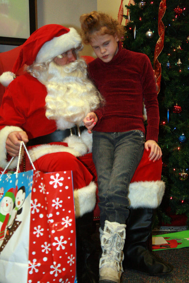 Bryanna Ward, 9, shares a quiet moment with Santa during the J.D. McCarty Center�s annual Christmas party.