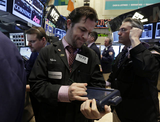 Trader Christopher Lotito, center, works on the floor of the New York Stock Exchange Wednesday, April 24, 2013. No sooner did a phony Associated Press report of explosions at the White House appear on Twitter on Tuesday than investors started dumping stocks, eventually unloading $134 billion worth. Turns out, some investors are not only gullible, they're impossibly fast stock traders. (AP Photo/Richard Drew)