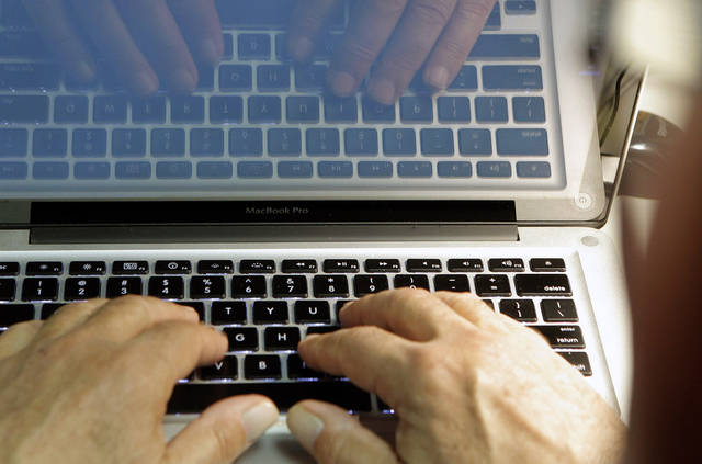 This photo illustration shows hands typing on a computer keyboard on Wednesday Feb. 27,2013. Security threats aren't new and have long been part of online life. But the increased attention on them offers a good time to review ways you can protect yourself. (AP Photo/Damian Dovarganes)
