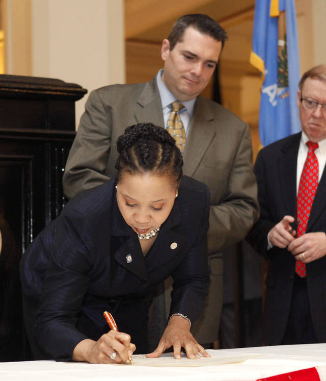State Rep. Anastasia Pittman, D-Oklahoma City, signs a proclamation Monday as Sen. Clark Jolley, R-Edmond, waits his turn. Legislators gathered to pray before their session started at the state Capitol in Oklahoma City. Photo By Paul Hellstern, The Oklahoman