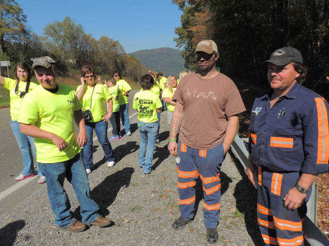 "Thomas Peak, center, and Allen Stapleton, right, join others at the United for Coal demonstration in Wise County, Va. on Saturday, Oct. 13, 2012, coming straight from work at a local coal mine. ""If coal gets shut down, everything's going to get shut down,"" said Peak of Big Stone Gap, his face still covered in coal dust. Groups of coal supporters that lined up sporadically along this Virginia highway were among thousands of people who turned out in at least three states to put a human face on an embattled industry. Its plight has become an issue in the presidential as well as in local and statewide races. (AP Photo/Debra McCown)"