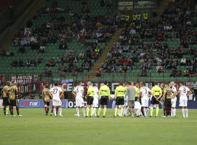 Roma and AC Milan players stand after referee Gianluca Rocchi stopped the match for a few minutes because of racist chanting directed at Italy striker Mario Balotelli by the visiting Roma fans during the Serie A soccer match between AC Milan and Roma at the San Siro stadium in Milan, Italy, Sunday, May 12, 2013. (AP Photo/Antonio Calanni)
