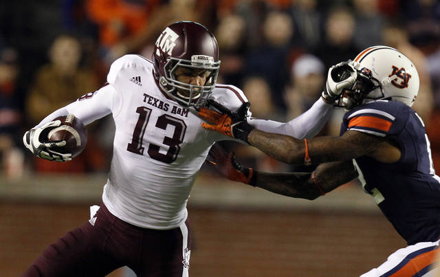 Texas A&M wide receiver Mike Evans (13) stiff-arms Auburn defensive back Demetruce McNeal (12) as he tries to reach the first-down marker during the first half of an NCAA college football game on Saturday, Oct. 27, 2012, in Auburn, Ala. (AP Photo/Butch Dill)