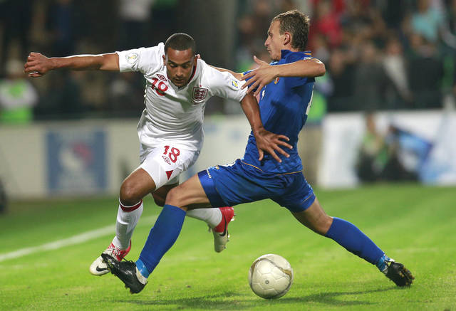 England's Theo Walcott, left, is challenged by Moldova's Alexandru Onica in Chisinau, Moldova, Friday, Sept. 7, 2012 during their Group H FIFA World Cup qualifier soccer match. (AP Photo/Vadim Ghirda)