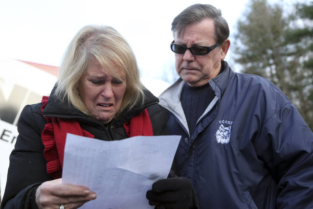 "Kathy Murdy, left, and her husband Rich Murdy react as they look at the list of victims of the Sandy Hook elementary school shooting, Saturday, Dec. 15, 2012 in Sandy Hook village of Newtown, Conn.  The victims of the shooting were shot multiple times by semiautomatic rifle, according to Connecticut Chief Medical Examiner  H. Wayne Carver II, M.D.  Carver called the injuries ""devastating"" and the worst he and colleagues had ever seen. Police began releasing the identities of the dead. All of the 20 children killed were 6 or 7 years old. Carver, said he examined seven of the children killed, and two had been shot at close range. When asked how many bullets were fired, he said, ""I'm lucky if I can tell you how many I found."" (AP Photo/Mary Altaffer) ORG XMIT: CTMA115"