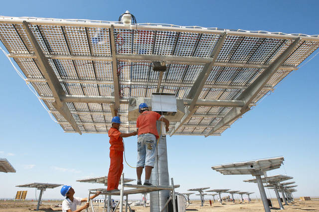 Workers install solar panels at a high-concentration photovoltaic power plant in Hami city in northwest China�s Xinjiang Uygur Autonomous Region.  AP Photo