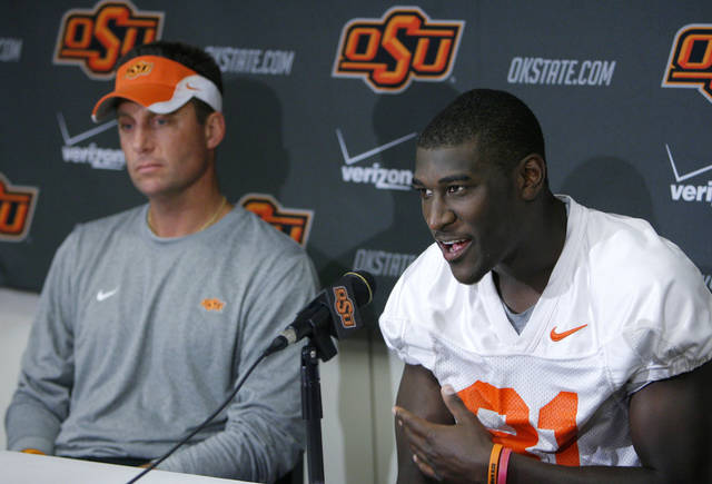 Oklahoma State football player Justin Blackmon, right, speaks to reporters while head coach Mike Gundy sits at his side during an NCAA college news conference in Stillwater, Okla., on Wednesday, Oct. 27, 2010. Coach Gundy says he has suspended star wide receiver Blackmon for one game after Blackmon's arrest on a misdemeanor DUI charge. (AP Photo/Tulsa World, Matt Barnard)