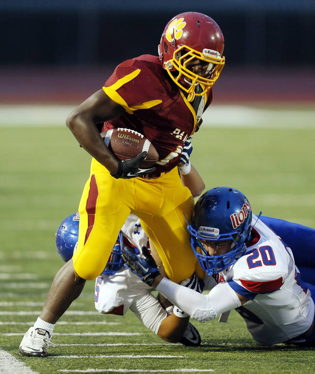 Moore's Chris Sanders (20) stops Putnam City North's Tae Moore (1) during a high school football game between Putnam City North and Moore at Putnam City Stadium in Oklahoma City, Thursday, Sept. 27, 2012. Photo by Nate Billings, The Oklahoman