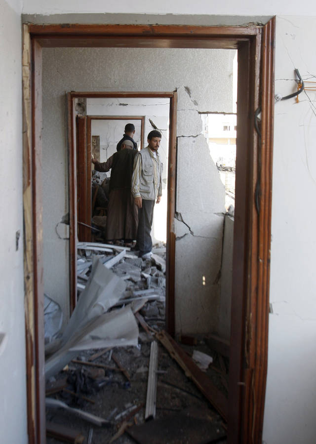 Palestinians inspect a damaged apartment hit in an Israeli strike, in Gaza City, Thursday, Nov. 15, 2012. Israeli aircraft, tanks and naval gunboats pounded the Hamas-ruled Gaza Strip and rocket salvoes thudded into southern Israel, as residents on both sides of the frontier holed up at home in anticipation of heavy fighting on the second day of Israel's offensive against Islamic militants. (AP Photo/Hatem Moussa)