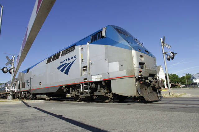 FILE - In this June 12, 2012, file photo an Amtrak commuter train moves through a crossing gate in Springfield, Ill., on its way to Chicago. From bridges to broadband, America�s infrastructure is supposed to be speeding along commerce, delivering us to work and piping energy and water into our homes and businesses. Romney shuns the idea that public-works spending is a good way to jumpstart the economy, saying decisions on worthy projects should be based on need and potential returns. He also wants to privatize Amtrak by ending federal subsidies for the money-losing passenger rail system. (AP Photo/Seth Perlman, File)