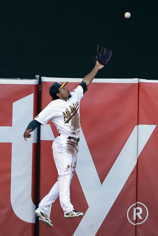 Oakland Athletics left fielder Coco Crisp makes a leaping catch on a ball hit by Detroit Tigers' Prince Fielder during the second inning of Game 3 of an American League division baseball series in Oakland, Calif., Tuesday, Oct. 9, 2012. (AP Photo/Marcio Jose Sanchez)