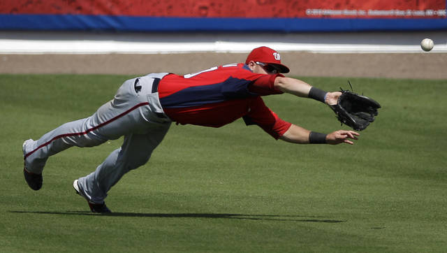 Washington Nationals right fielder Corey Brown makes a diving catch for the out on a ball hit by New York Mets' Vinny Rottino in the ninth inning of a spring training baseball game in Port St. Lucie, Fla., Wednesday, March 28, 2012. Washington won 3-2. (AP Photo/Patrick Semansky)