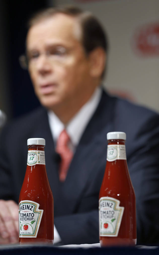 H.J. Heinz Co. CEO William Johnson, is seen behind two bottles of Heinz ketchup as he speaks at a news conference at the world headquarters of the H.J. Heinz Co. on Thursday, Feb. 14, 2013, in Pittsburgh. Billionaire investor Warren Buffett�s Berkshire Hathaway and its partner on the deal. 3G Capital, are dipping into the ketchup business as part of a $23.3 billion deal to buy the Heinz ketchup company. (AP Photo/Keith Srakocic)