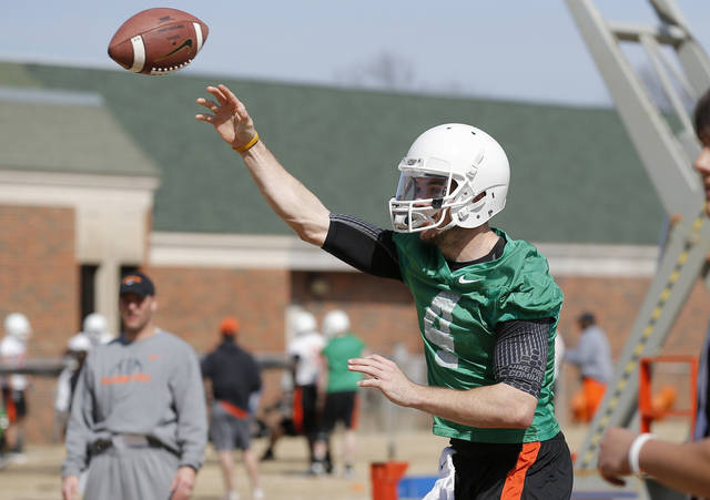 OKLAHOMA STATE UNIVERSITY / OSU / COLLEGE FOOTBALL: Oklahoma State quarterback J.W. Walsh throws a pass as offensive coordinator Mike Yurcich watches during an OSU spring football practice in Stillwater, Okla., Wednesday, March 13, 2013. Photo by Bryan Terry, The Oklahoman