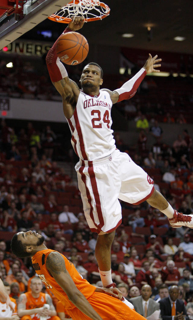 Oklahoma's Romero Osby (24) is called for a charge against Oklahoma State's Michael Cobbins (20) as he dunks during the Bedlam men's college basketball game between the University of Oklahoma Sooners and the Oklahoma State Cowboys in Norman, Okla., Wednesday, Feb. 22, 2012. Photo by Bryan Terry, The Oklahoman