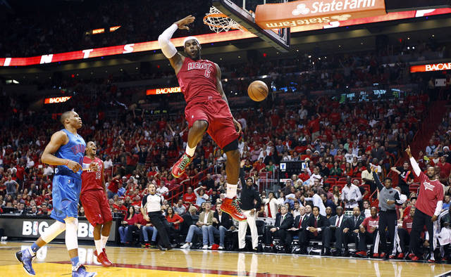 Miami Heat's LeBron James (6) dunks as Oklahoma City Thunder's Russell Westbrook (0) and Heat's Mario Chalmers (15) watch during the first half of an NBA basketball game, Tuesday, Dec. 25, 2012, in Miami. (AP Photo/J Pat Carter) ORG XMIT: FLJC101